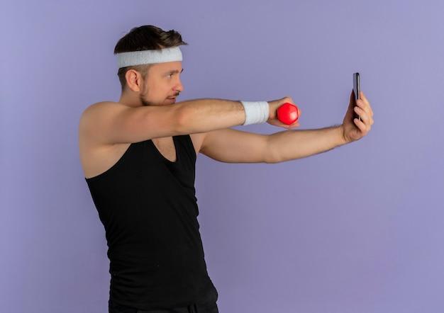 紫色の壁の上に立ってダンベルを手にポーズをとって彼のスマートフォンを使用してselfieを取るヘッドバンドを持つ若いフィットネス男