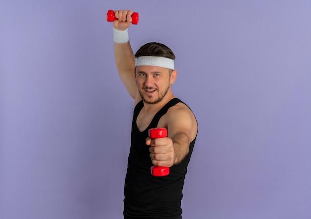 Giovane uomo di forma fisica con la fascia che risolve con il dumbbell che sembra fiducioso in piedi sopra la parete viola