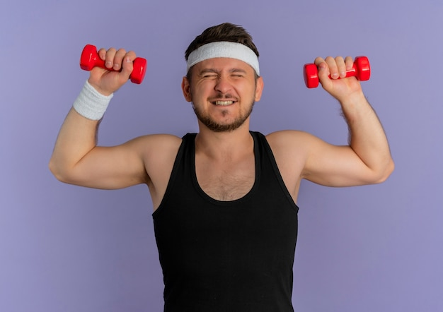 Giovane uomo fitness con archetto lavorando con manubri guardando fiducioso e teso in piedi su sfondo viola