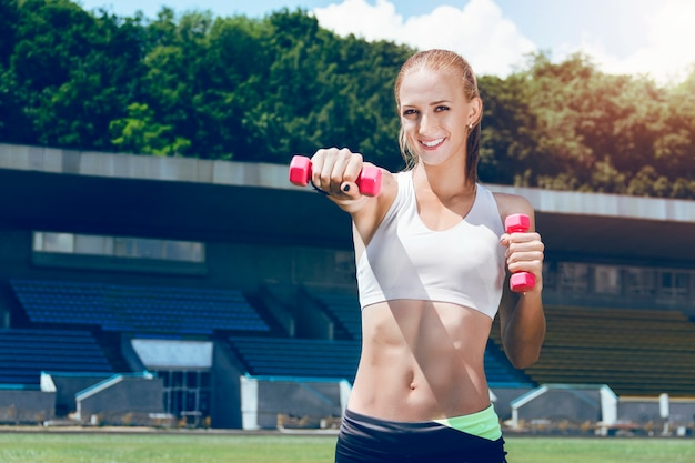 Young fitness muscle sporty woman holding pink hand weights.