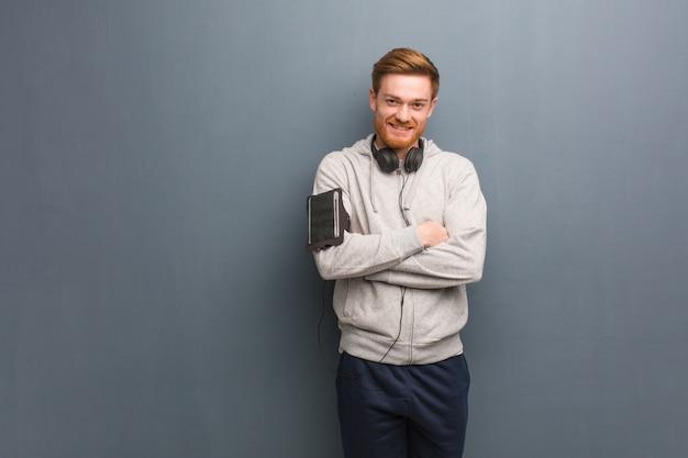 Молодой фитнес рыжий мужчина скрещивание рук, улыбаясь и расслабленным
