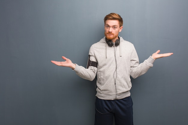 Young fitness redhead man doubting and shrugging shoulders