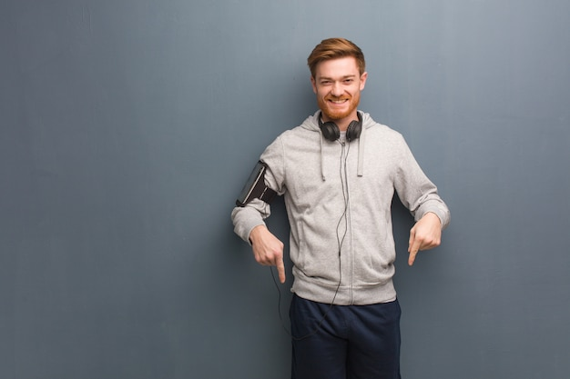Young fitness redhead man pointing to the bottom with fingers