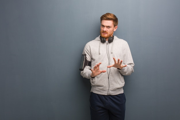 Young fitness redhead man rejecting something doing a gesture of disgust