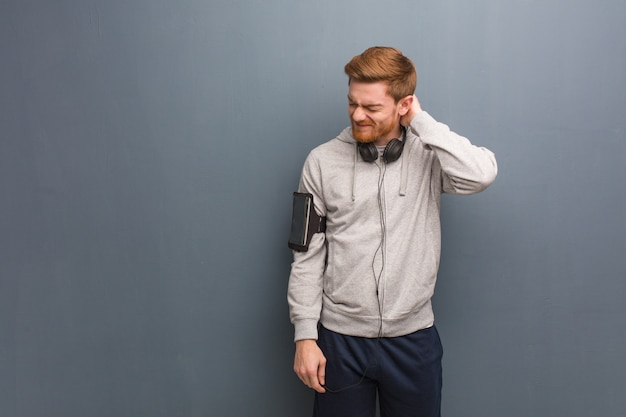 Young fitness redhead man suffering neck pain