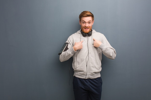 Young fitness redhead man surprised, feels successful and prosperous