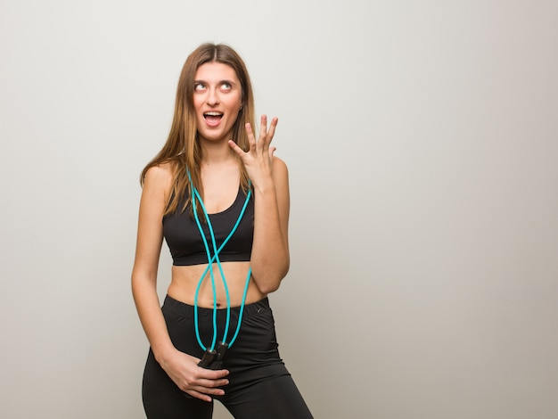 Young fitness russian woman angry and upset. holding a jump rope.