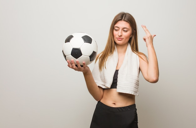 Young fitness russian woman doing a suicide gesture. holding a soccer ball.