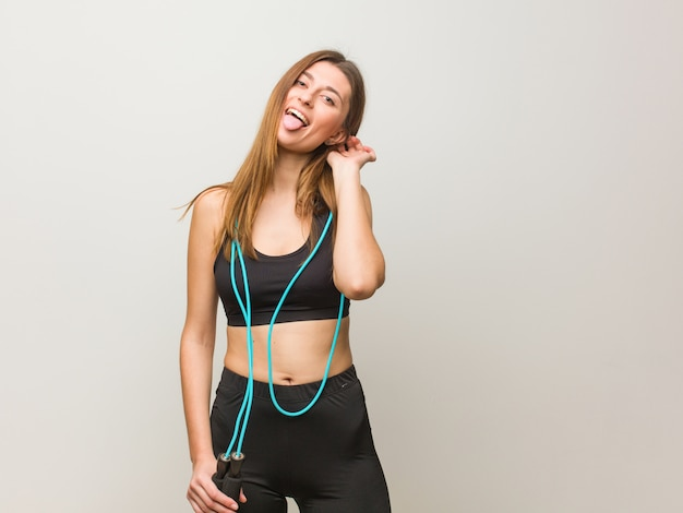 Young fitness russian woman funnny and friendly showing tongue. holding a jump rope.