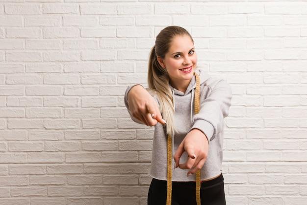 Молодая женщина фитнеса держа ленту измерения