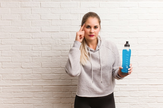 Young fitness russian woman holding a energy drink