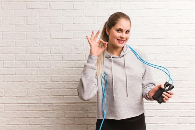 Young fitness russian woman holding a jump rope against a bricks wall