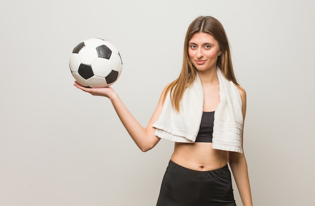 Young fitness russian woman holding something with hand. holding a soccer ball.