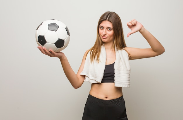 Young fitness russian woman pointing fingers, example to follow. holding a soccer ball.