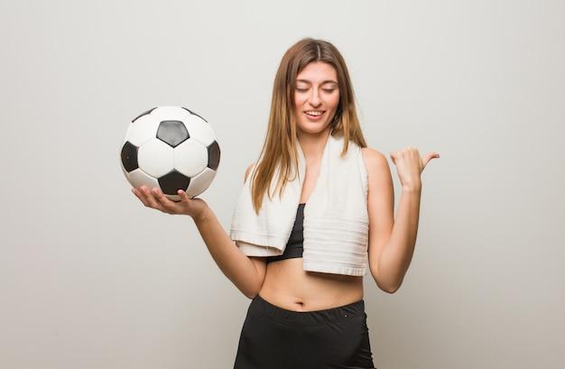 웃 고 측면을 가리키는 젊은 피트 니스 러시아 여자. 축구 공을 들고.
