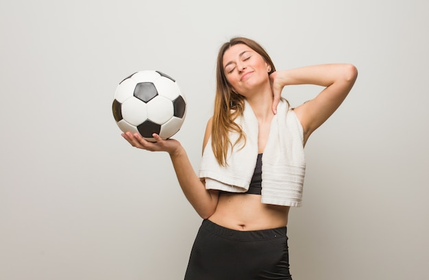 Young fitness russian woman suffering neck pain. holding a soccer ball.