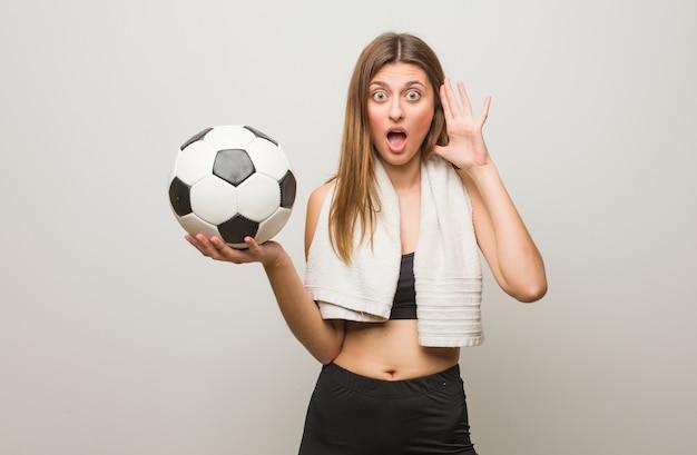 Молодая русская женщина фитнеса удивлена и шокирована. держит футбольный мяч.