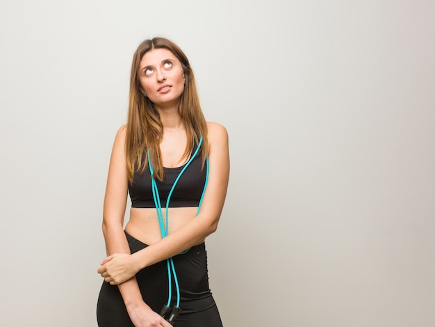 Young fitness russian woman tired and bored. holding a jump rope.