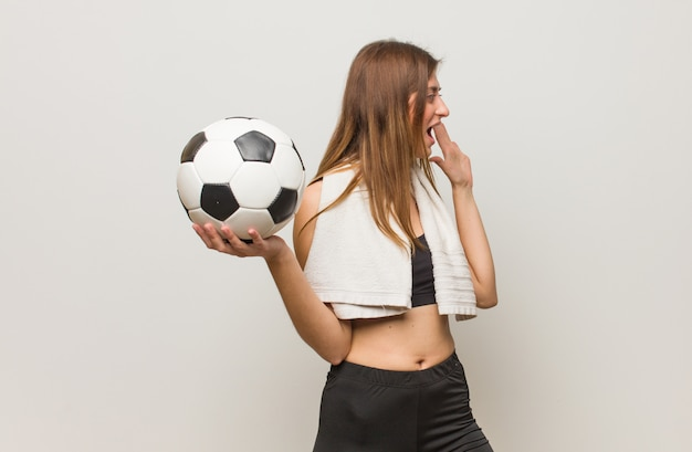 Young fitness russian woman whispering gossip undertone. holding a soccer ball.