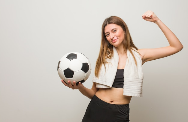 Young fitness russian woman who does not surrender. holding a soccer ball.