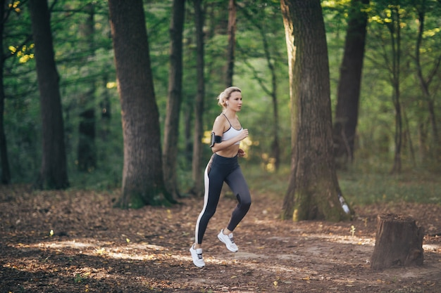 Young fitness sport woman running on the forest road in the morning