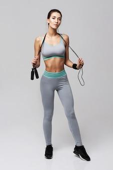 Женщина молодого фитнеса sportive представляя держащ скача веревочку на белизне.