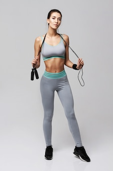 Young fitness sportive woman posing holding jumping rope on white.