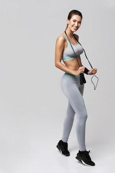 若いフィットネススポーツ女性が笑みを浮かべてポーズを保持している白の縄跳び。