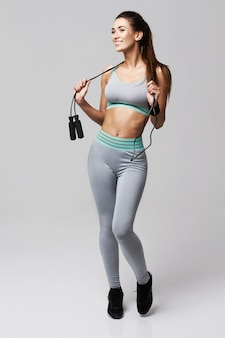 Young fitness sportive woman posing smiling holding jumping rope on white.