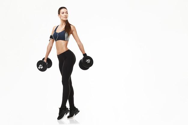 Donna sportiva di giovane forma fisica in cuffie che prepara le teste di legno della tenuta su bianco.