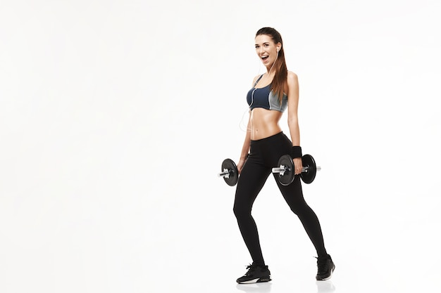 Женщина молодого фитнеса sporty в наушниках тренируя держащ гантели на белизне.