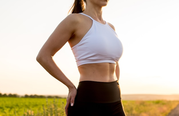 Молодой фитнес спортивный женщина позирует в спортивной одежде и расслабляющий после тренировки. крупным планом показывает сильный пресс.