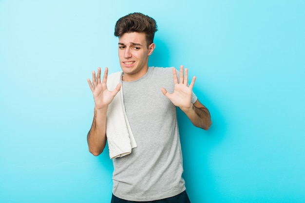 Young fitness teenager man rejecting someone showing a gesture of disgust.