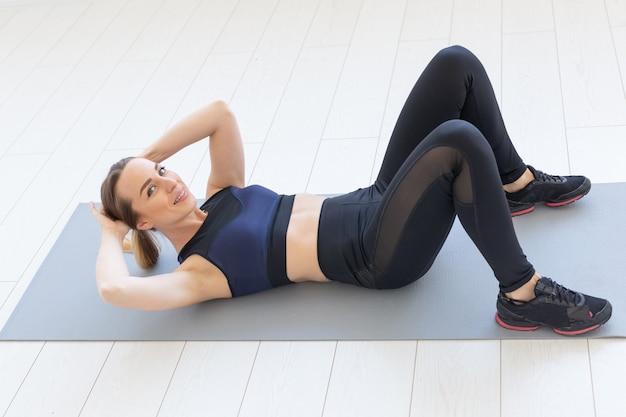 自宅の床で腹筋クランチ運動をしている若いフィットネス女性