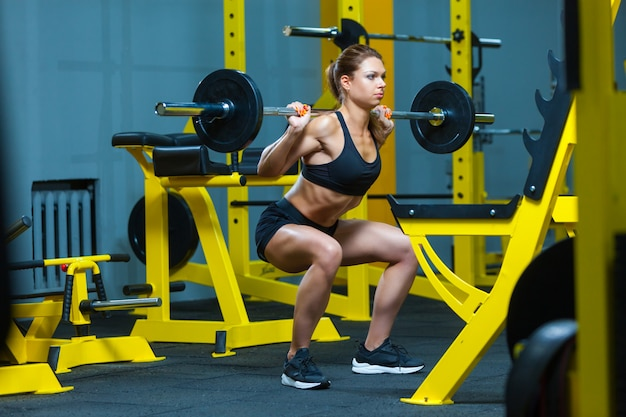 Young fitness woman doing barbell squats in a gym.