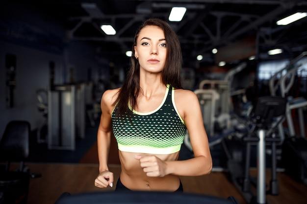 Молодой фитнес женщина делает кардио упражнения в тренажерном зале на беговой дорожке.