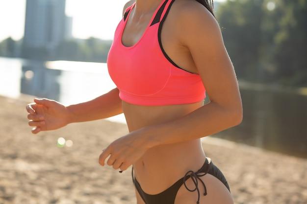ビーチで有酸素運動をしている若いフィットネス女性。クローズアップショット