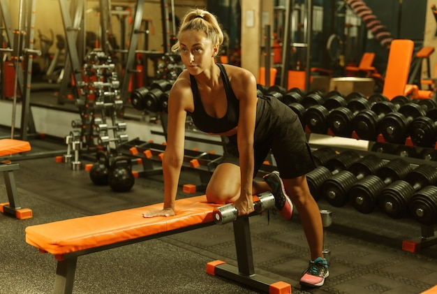 Young fitness woman doing dumbbell traction with one hand tilted from a bench in the gym. training concept with free weights.