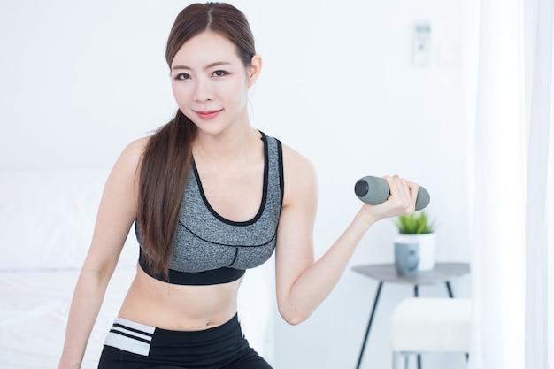 Молодая женщина фитнеса делает упражнения с гантелями
