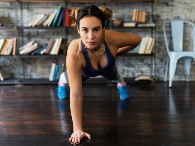 밀어 넣기를 수행하는 젊은 피트 니스 여자는 바닥에 한 손으로 운동을 올린다