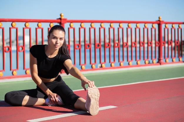 스트레칭을 하고 다리에서 달리기를 준비하는 젊은 피트니스 여성. 텍스트를 위한 공간
