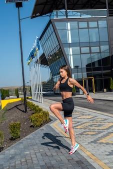 近代的な都市の建物の近くでストレッチヨガの練習をしている若いフィットネス女性。健康的な生活様式