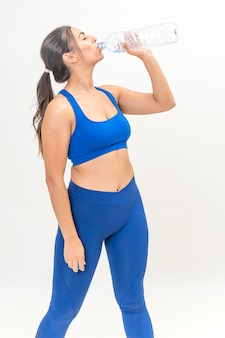 Young fitness woman drinking from a bottle of water dressed in sportswear