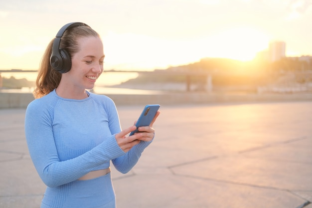 Young fitness woman finish running in the city. enjoy listening music with headphones, while holding phone. sunset. healthy lifestyle. freedom. outdoor workout. high quality photo