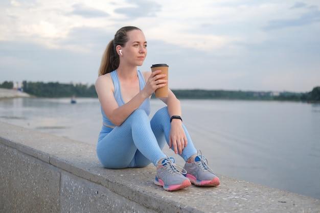 젊은 피트 니스 여자 도시에서 실행 완료. 이어폰으로 음악을 들으면서 커피를 즐겨보세요. 일몰. 건강한 생활. 자유. 야외 운동. 고품질 사진