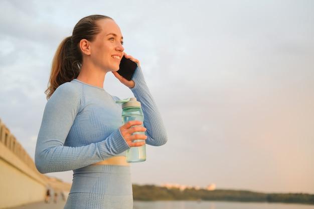Молодая женщина фитнеса заканчивает бежать в городе. пейте воду во время разговора по телефону. закат. здоровый образ жизни. свобода. тренировки на свежем воздухе. фото высокого качества