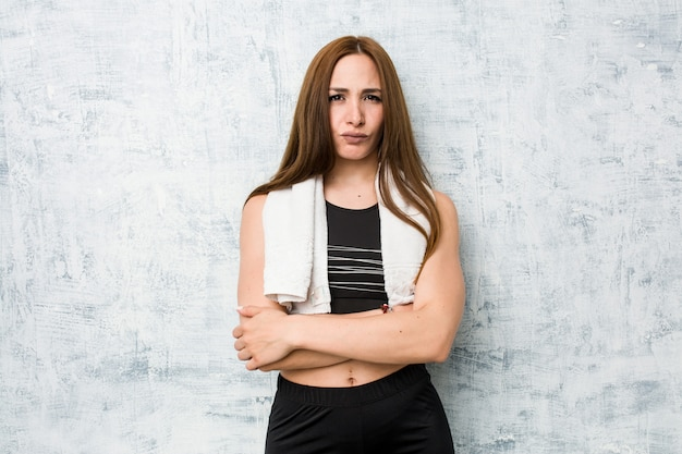 Young fitness woman frowning face in displeasure, keeps arms folded.