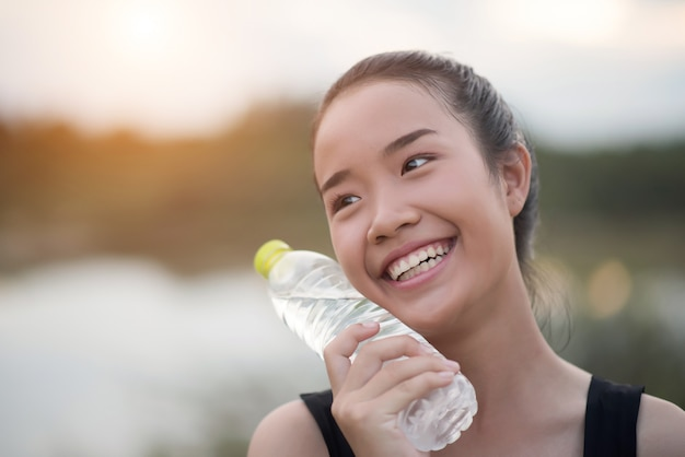 Young fitness woman hand holding water bottle after running exercise