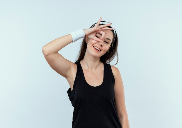 Young fitness woman in headband doing ok sign with fingers looking at camera through this sign smiling standing over white background