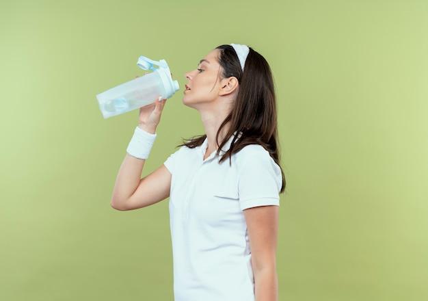 Giovane donna fitness in acqua potabile fascia dopo allenamento in piedi su sfondo chiaro